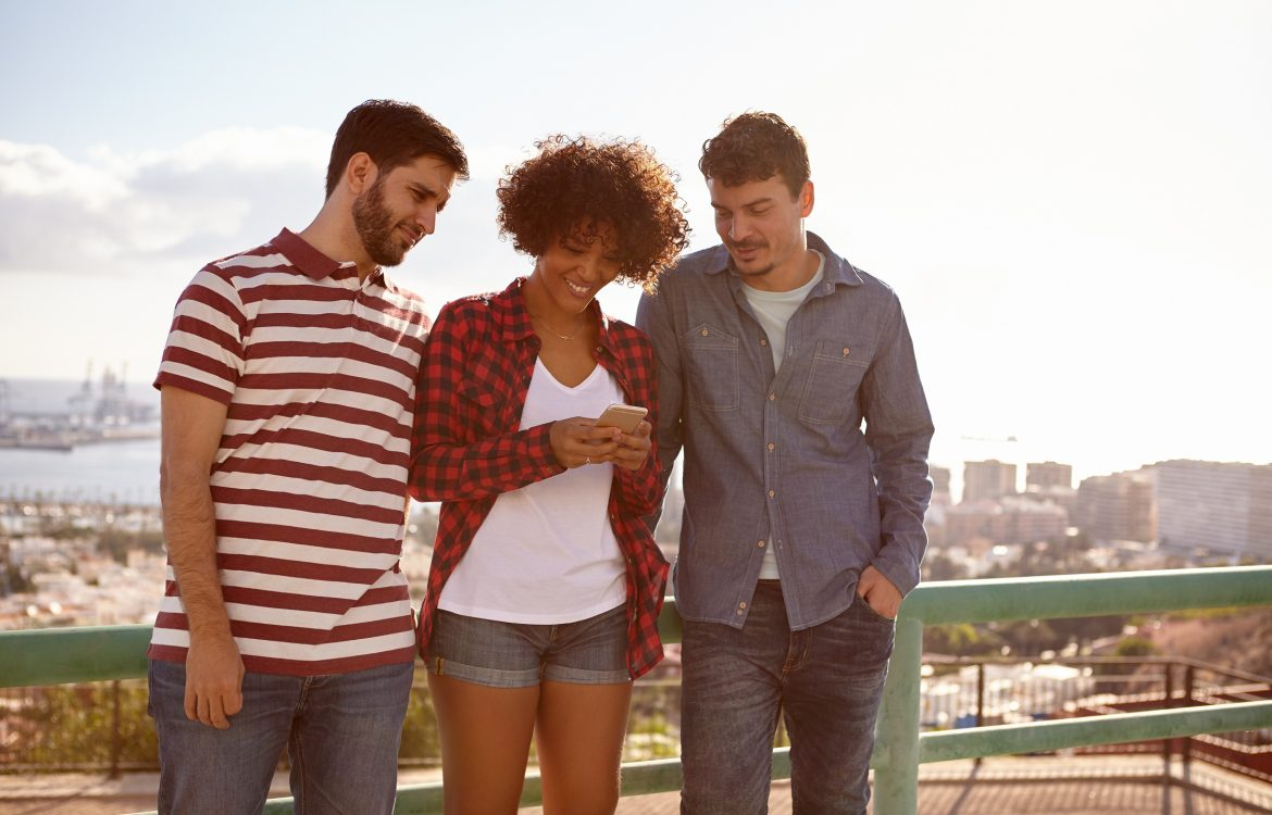 A girl and two guys reading a message on a cell phone while standing against a railing with a city scape behind them